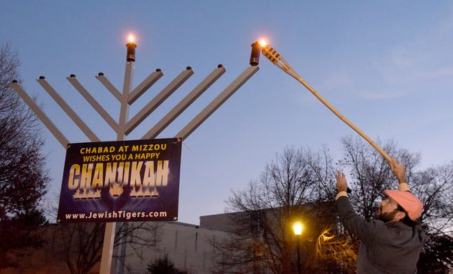 Ben Trachtenberg, professor at the University of Missouri School of Law, lights the first candle of the menorah after lighting the shamash center candle on Thursday to begin the eight-day Jewish Festival of Lights at MU Speakers Circle.