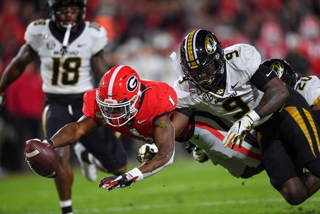 Georgia wide receiver George Pickens (1) dives into the end zone for a touchdown past Missouri safety Tyree Gillespie (9) during a game Nov. 9, 2019, at Sanford Stadium in Athens, Ga.