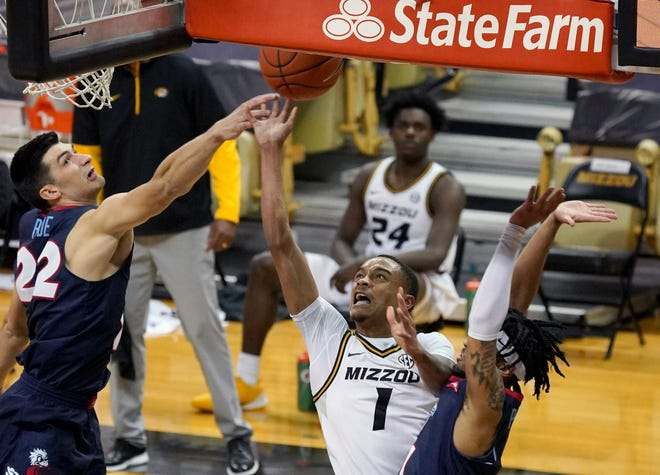 Missouri guard Xavier Pinson (1) shoots as Liberty forward Kyle Rode (22) defends during a game Wednesday at Mizzou Arena.