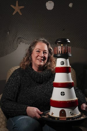 """Susan Delgado poses for a portrait with a terra cotta lighthouse she made on Dec. 10 in New Albany. Delgado, a local Scientologist, built a lighthouse fixture for gardens for a video series """"Scientologists @ Home"""" to show what Scientologists are doing to stay happy during the pandemic"""