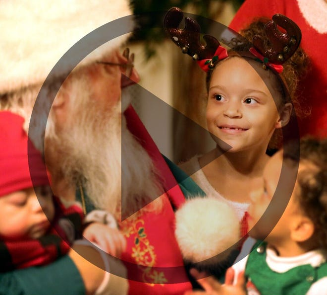 In this file photo, Azzanna Prater, 6, surrounded by her siblings, looks up at Santa Claus, (Richard Knapp) at the Open Shelter Christmas event, where children could pick out toys, December 18, 2018. Azzanna, who has seen Richard for the past several years was enamored with him and her mother says, believes he is the real Santa and the mall Santas are fake.