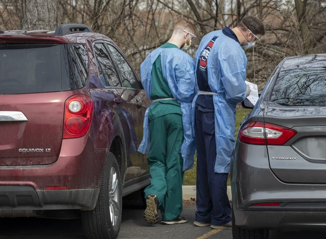 Employees of Ohio State University Wexner Medical Center administer a virus test to a person waiting in his car.