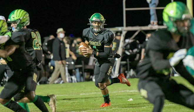 Lake Minneola's Robbie Sanders (1) looks for a receiver in last week's Class 6A-Region 2 championship game against Tampa Gaither at the Hawks Nest in Minneola . [PAUL RYAN / CORRESPONDENT]