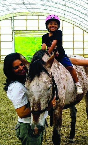 MAE Organization for the Homeless Founder Martinha Isabel Javid interacts with a child benefitting from equine therapy, one of the many programs offered by her organization.
