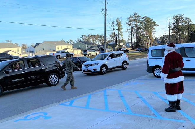 """Parents and children living in on base housing managed by Atlantic Marine Corps Communities drive by to see Santa Claus during Wednesday's """"Home for the Holidays"""" event held on Camp Lejeune."""