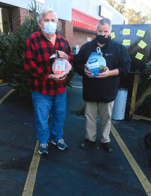 David Jackson, president of the Moss Hill Ruritans, accepts the donation of a ham and turkey from John King, manager of the Jackson Heights Piggly Wiggly, to feed four needy families for Thanksgiving and Christmas. [CONTRIBUTED PHOTO]