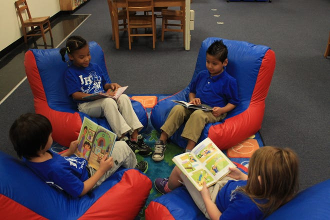 A group of students at Janie Howard Wilson Elementary School read books in a classroom.