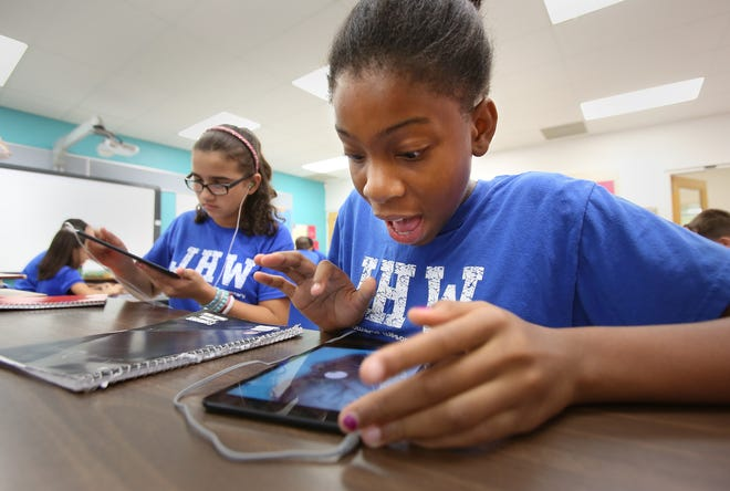 Students in the IGNITE Academy at Janie Howard Wilson Elementary work on a class project as Disney Imagineers creating a theme park ride based on a system of the human body using their iPad minis in 2013.