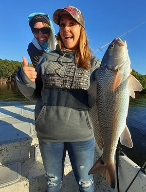 Jacinda Rose, left, of Lake Panasoffkee and Stacey Hasty of Inglis smile as they show off a good size redfish Hasty caught near Cyrstal River while fishing with Capt. Marrio Castello, of Tall Tales Charters on Tuesday.