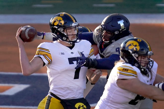 Iowa quarterback Spencer Petras is pressured by Illinois defensive lineman Roderick Perry II during the first half of a game against Illinois on Saturday, Dec. 5, 2020, in Champaign.