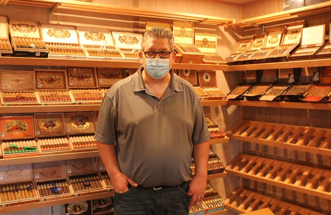 Ron Reed, owner of Breakwaters Cigar and Whiskey Lounge, stands inside his 12-foot-by-12-foot humidor.