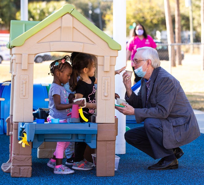 """Mina Novak, 2, gives Stan Hanson a cup of tea on Thursday from the kitchen at the new playground at Episcopal Children's Services in Ocala. ECS dedicated the playground at the Thelma Griffith Early Head Start Center in honor of philanthropists Stan and Martha Hanson and in memory of their son, Adam, who passed away in 2006. After the Hansons attended a tour of ECS facilities last year, they inquired about projects needing priority attention, and the playground renovation were discussed. """"We went to the playground and once we saw the smiles of the youngsters using it, the project received a 'let's do it' from Martha and me!"""" Stan Hanson explained. The Hansons donated $50,000 to the center to help with the renovations. The playground was installed in April of this year and serves 80 children who attend the center each day."""