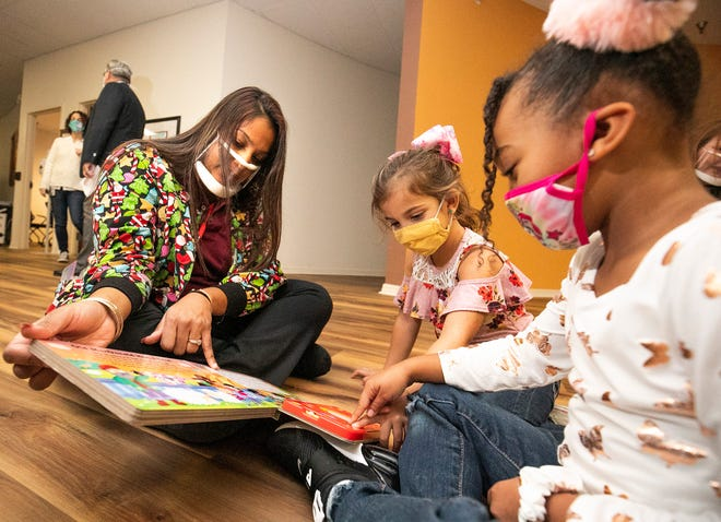 Tabitha Woolbright, director of Future Stars Academy of Ocala, reads an interactive book to Abigail Truesdell, 4, center and Avianna Velasquez-Rhodes, 5, right, on Thursday at the Early Learning Coalition of Marion County. The Kiwanis Club of Ocala and the Early Learning Coalition have purchased six cases of ClearMask, which allow the face of caregivers to be visible for babies and toddlers, and thus allowing the children to observe their caregivers' expressions and nonverbal cues.