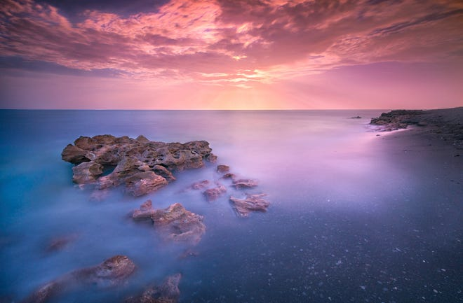 """Stock shot this photo titled """"Coral Moonrise"""" at the Blowing Rocks Preserve in Jupiter Island. The picture, taken during a three-minute exposure, features a full moon made to look like the sun."""