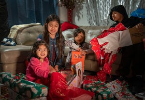 From left: Jessica Guzman, Emily Morales, Anai Raymundo, and Jonathan Morales open gifts donated to them at a home in Riviera Beach on Thursday.  Jessica and Anai's mother, Catarina Reymundo Marcos, was killed by a hit-and-run driver in September. GREG LOVETT / THE PALM BEACH POST