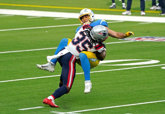 Chargers tight end Hunter Henry is tackled by New England defensive back Kyle Dugger (35) during the first half on Sunday's game at SoFi Stadium. Dugger has stayed in touch with safety Patrick Chung — who opted out of playing due to the pandemic — this season.