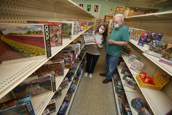 Debbie and Larry Donohue pull out one of the better sellers in the puzzle aisle at their store  Ben's Variety & Framing in Canton.