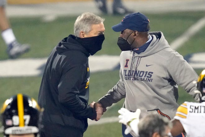 Iowa head coach Kirk Ferentz, left, and Illinois head coach Lovie Smith shake hands after their game on Saturday in Champaign. Iowa won 35-21. The Illini take on rival Northwestern this Saturday in Evanston.