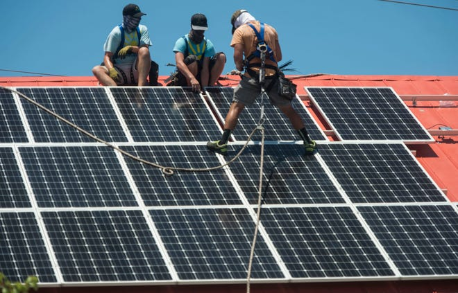 Workers in Englewood install solar panels. Solar United Neighbors, a nonprofit, is hosting a Zoom information session on Tuesday at 6 p.m.