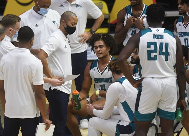 UNCW head men's basketball coach Takayo Siddle talks to his team during a break in the action against St. Andrews at Trask Coliseum Wednesday, December 9, 2020. This was the first home game of the season for the men's team.   [MATT BORN/STARNEWS]
