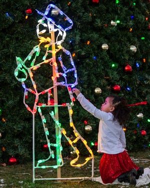 Gwendolyn Mongeau, 4, touches lights on the Worcester Common as her mother tries to take a picture for a Christmas card Thursday.