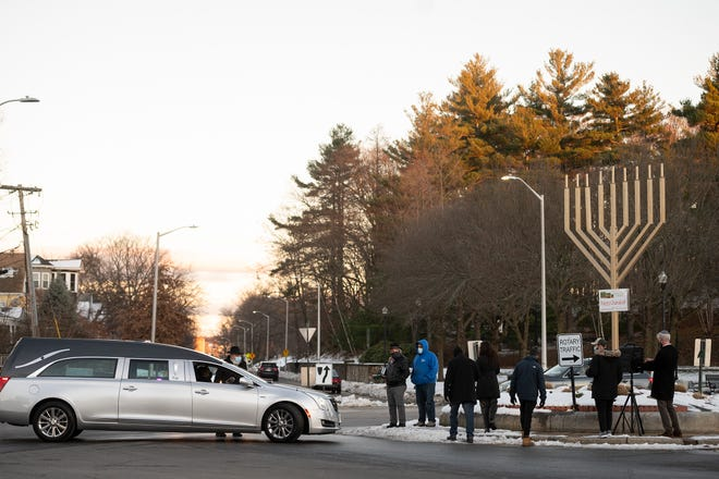 WORCESTER - Mourners gather Thursday at Newton Square for a menorah lighting ceremony in honor of Arthur Herring, who died Wednesday, as a hearse carrying Herring's body processes past the square on the the first night of Hanukkah. Herring created the square's menorah.