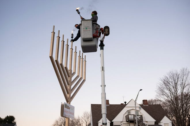 WORCESTER - Perry Spiro, 23, the grandson of the late Arthur Herring, the man who created Newton Square's menorah, lights it Thursday for the first night of Hanukkah. Herring, who died Wednesday, was honored during the ceremony.