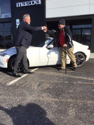 The general manager of Flow Mazda Marty Edwards gives John Goubeaux the key to his new Mazda MX-5 Convertible.[Fayetteville Observer photographer Melody Brown-Peyton