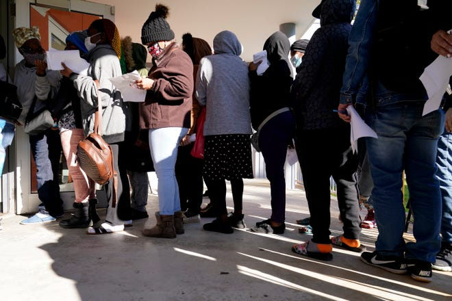 People wait in line to receive a $250 grocery gift card available to Miami residents experiencing hardship and food insecurity due to COVID-19, on Dec. 8 in Miami. The CARES Act provides funding for the cards.