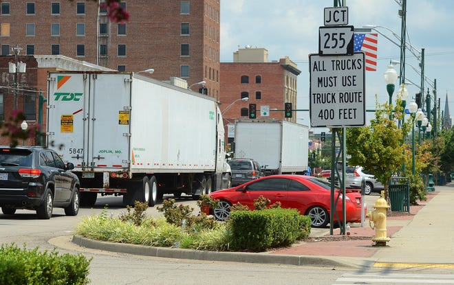 Trucks move east through downtown Fort Smith in 2017. Halff Associates and Central Business Improvement District Commissioner Phil White have proposed reroute ideas for trucks in the downtown area. [TIMES RECORD FILE PHOTO]