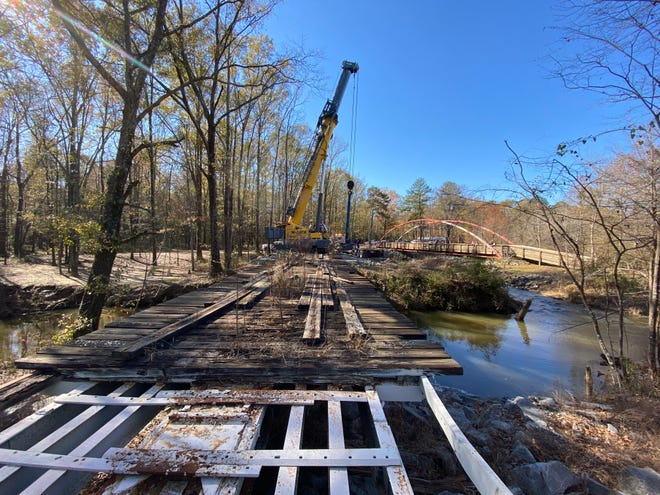 A crew from McAbee Construction set a historic bridge in place in Van De Graaf Arboretum and Historic Bridge Park in Northport Thursday, Dec. 10, 2020. [Staff Photo by Gary Cosby Jr.]
