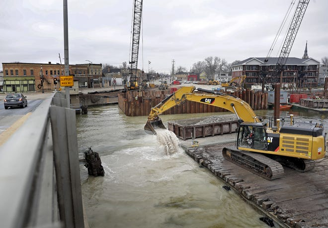 Construction crews use a barge and backhoe to dredge the bottom of the Fox River in preparation for the construction of a new $33 million Racine Street bridge in Menasha.
