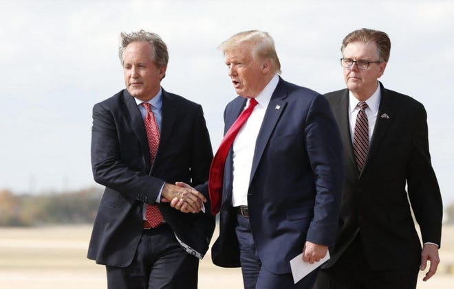 Texas Attorney General Ken Paxton, left, greets President Donald Trump at Austin Bergstrom International Airport in November 2019. Lt. Gov. Dan Patrick is at right.
