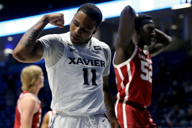 Xavier Musketeers guard Dwon Odom (11) reacts after scoring and drawing a foul from Oklahoma Sooners forward Kur Kuath (52), background, in the first half of a men's NCAA college basketball game, Wednesday, Dec. 9, 2020, at Cintas Center in Cincinnati.