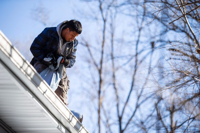 Workers from Roberto's Roofing replace the roof on the first home in the Highland Park Community Development Association's affordable housing initiative, on Wednesday, Dec. 10, 2020, in Des Moines. The work on the home has continued as the group has been able to fundraise and receive grants.