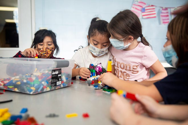 From left, Emely Longoria, Miley Guerrero and Mckenna Hill play with Legos in the Highland Park Community Development Association's Precious Beginning Children's Center kindergarten and first-grade room Wednesday, Dec. 9, 2020, in Des Moines.