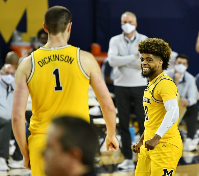 Guard Michigan Mike Smith (12) dan center Hunter Dickinson (1) bereaksi di babak kedua. Michigan vs Toledo di Crisler Center di Ann Arbor, Mich. Pada 9 Desember 2020. Michigan menang 91-71.