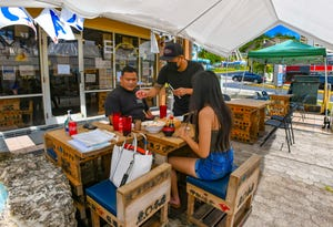 Server Limuel Yumang checks on Benny Quinata and his daughter, Avah Quinata, during their outdoor dining experience under a canopy at the Uomaru Restaurant in Tumon in this Dec. 10 file photo.
