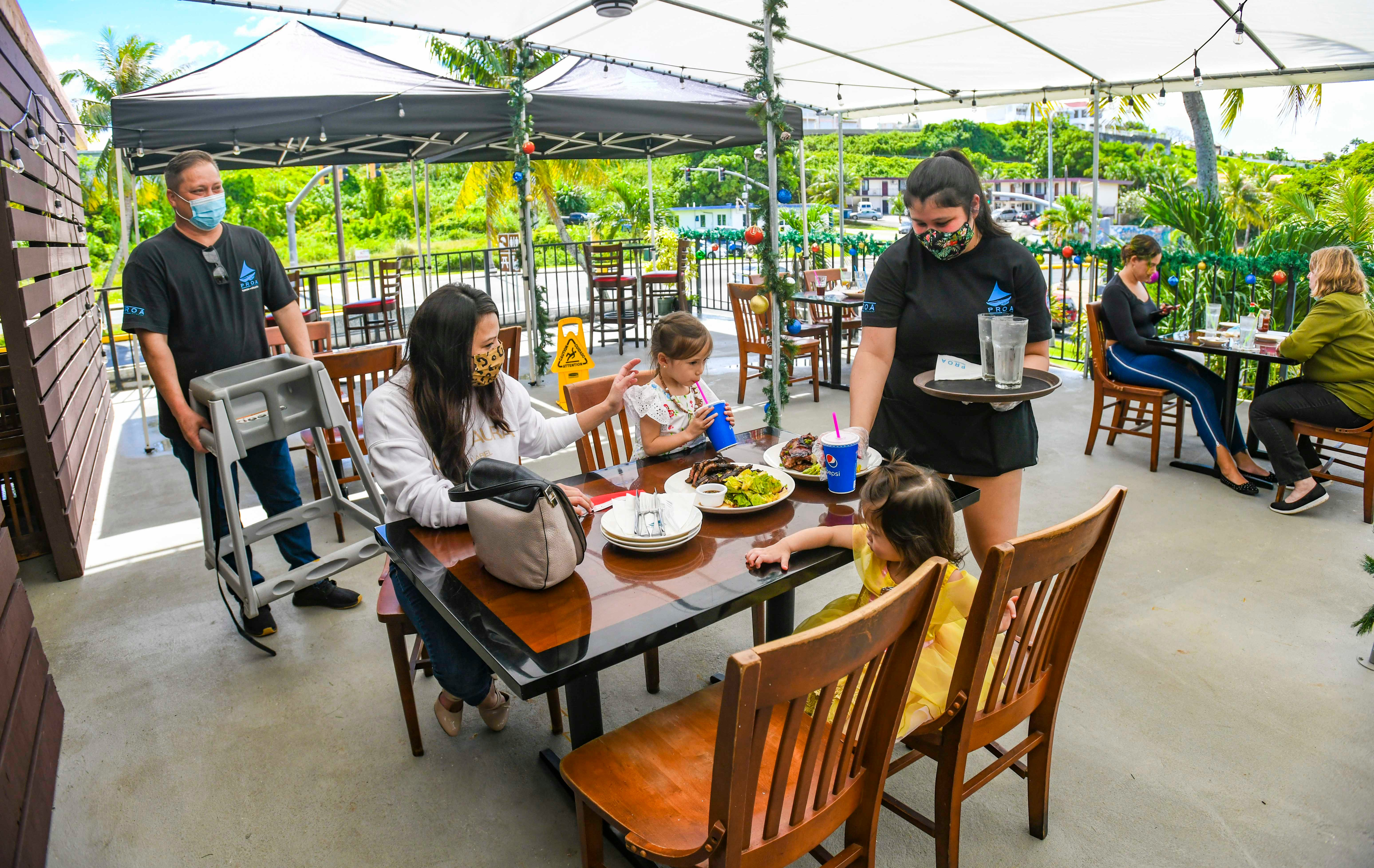 Michele Catahay Perez prepares to enjoy a midday meal with her daughters on the second-floor outdoor dining area of Proa Restaurant in Tumon, as Geoffery Perez, the girls' father and owner of the eatery, prepares to join them on Thursday, Dec. 10, 2020.