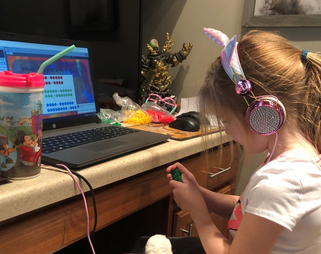 Evie Knudtson of Sun Prairie listens to her teacher through headphones as she works with colored blocks as part of a math lesson. Knudtson, 7, is a first-grader enrolled at Wisconsin Virtual Academy.