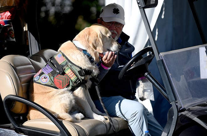 A Wounded Warrior golfer pets his support dog during the QBE Shootout Pro-Am at Tiburón Golf Club in Naples on Thursday, December 10, 2020.