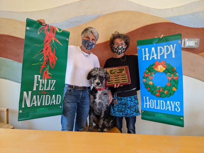 Janey Katz, left, and Suzi Calhoun pose with the with their dog Piper and the Spirit of Christmas Award.