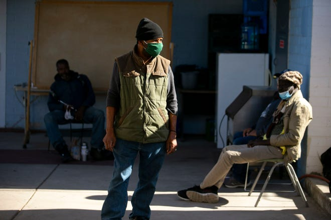 Zachery Walker, 60 (center), stands in the yard at the Justa Center, a day center for homeless people aged 55 and over, in Phoenix on Dec. 9, 2020.