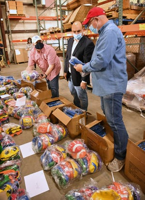 Wichita Falls Optimist Club members Matt English, left, Matt Yell and Jeff Pendley look over hundreds of balls and other physical education equipment purchased for the Wichita Falls ISD schools with the club's donation.