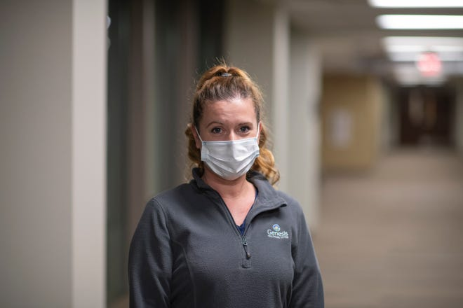Carrie Cochran works on the respiratory unit at Genesis Hospital. She wears a medical-grade mask when off-duty and an N-95 mask when she treats the COVID-19 patients at Genesis Hospital. The N-95 masks along with medical gowns, face shields and latex gloves are the suits of armor frontline nurses wear each day as they care for their patients.