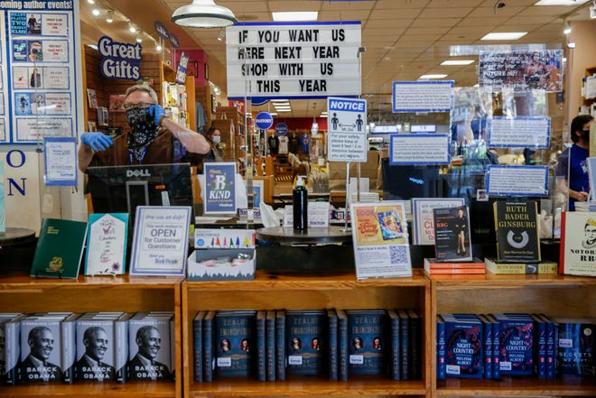 Will Kinsley answers phone calls while behind a plexiglass barrier at BookPeople on Dec. 10. The store has reopened with pandemic protocols in place.