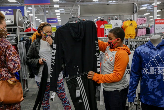 Kaidon Brown-Smith, 10, shows his mother, Renee Milam, a track suit while shopping at the Academy Sports and Outdoors store on Brodie Lane. For Milam, it was about getting as many clothes and shoes as she could for the family of five. The family was one of four that received a $2,000 shopping spree from Academy in preparation for the holidays.