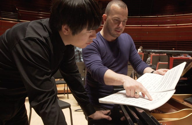 Philadelphia Orchestra Conductor Yannick Nezet Seguin (right) and Chinese pianist Lang-Lang confer during a practice session for the Philadelphia Orchestra visit to China. Jennifer Lin of Doylestown has made a documentary on the orchestra's visits there.