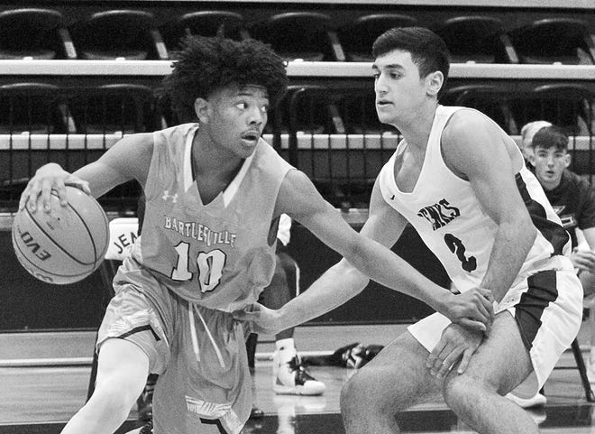 Bartlesville High freshman David Castillo, left, drives past a Jenks High defender during  recent varsity basketball action.
