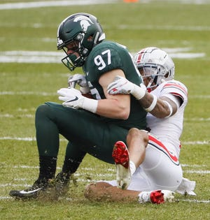 Ohio State safety Ronnie Hickman tackles Michigan State tight end Tyler Hunt short of a first down in the Buckeyes' win Saturday.